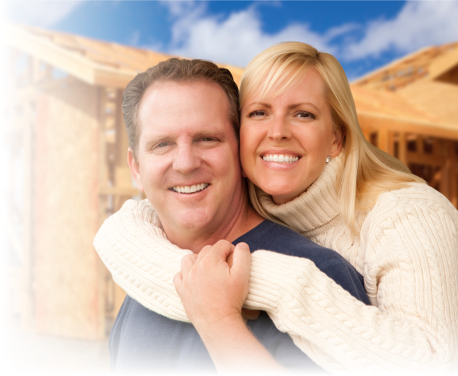 Man and woman hugging in front of their home construction project